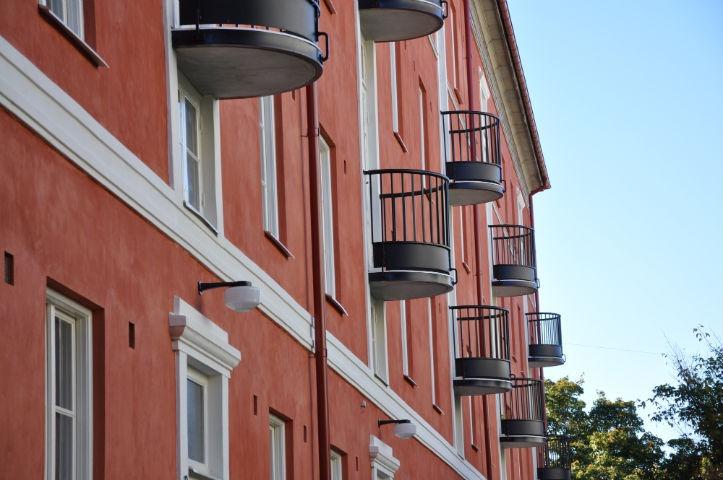 Närbild av röd putsad fasad med välvda balkonger