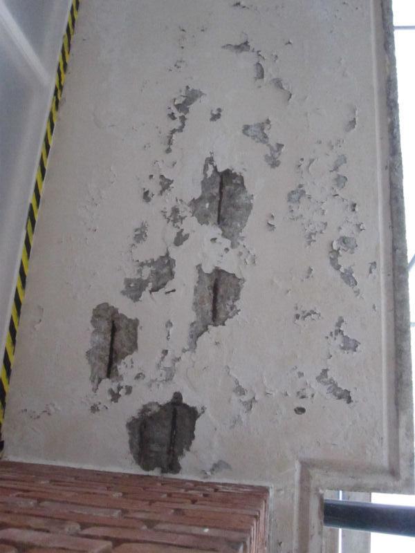 De olika stegen vid betongrenovering. Här har de grå armeringsjärnen börjat rosta och träder fram genom den vita färgen