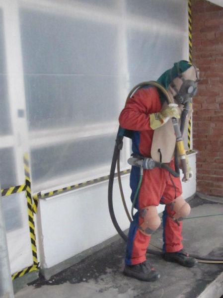 Nästa steg vid betongrenovering. Färg från balkongplattorna blästras bort.
