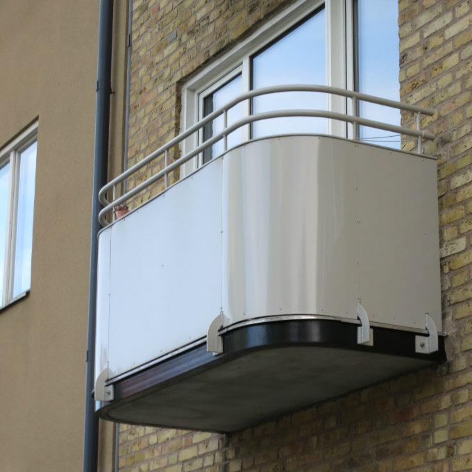 Närbild på benvit balkong mot en gul fasad, vid balkongrenovering vid nobeltorget