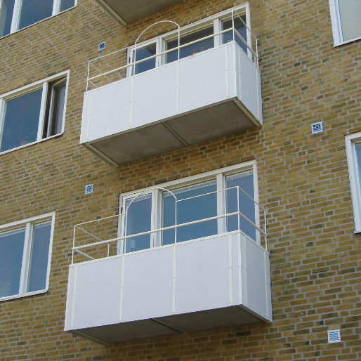 Vita balkonger mot en gul tegelfasad vid balkongrenovering i Malmö