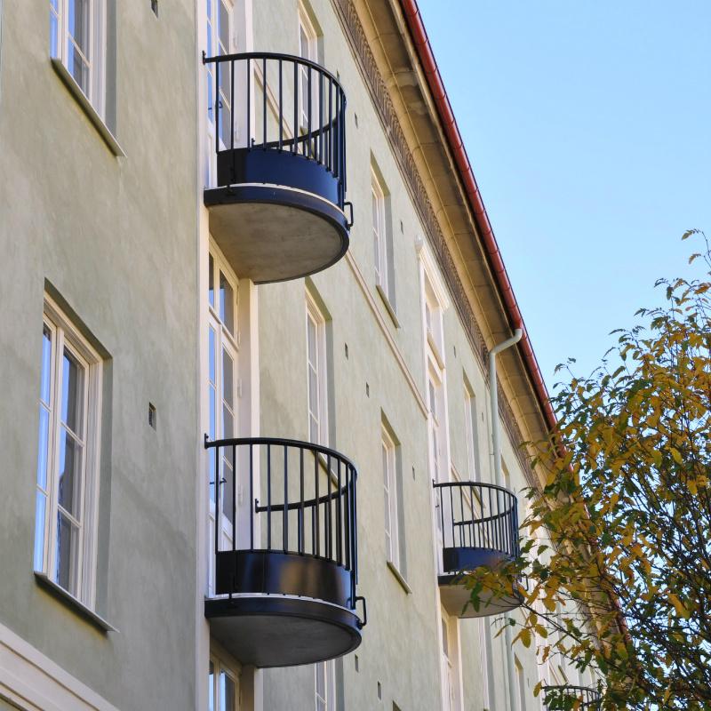 Svarta välvda balkonger mot en grå fasad vid ballkongrenovering på BRF Solhus