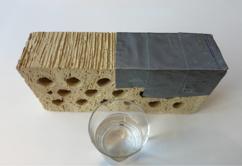 Experiment med hydrofobering: Tegelstenens vänstra sida har blivit hydrofoberad, medan den högra täckts över för att hållas obehandlad