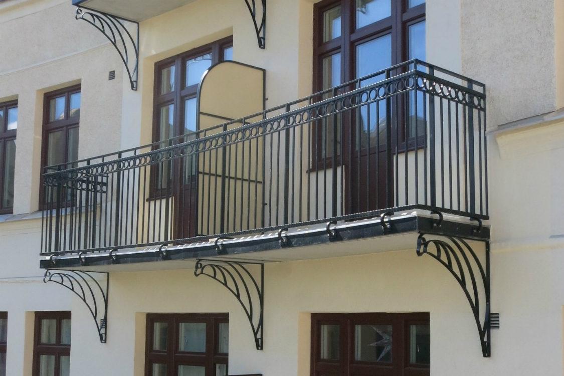 Balkong med svarta smidesräcken mot gul fasad vid balkongrenovering på Kristianstadsgatan i Malmö