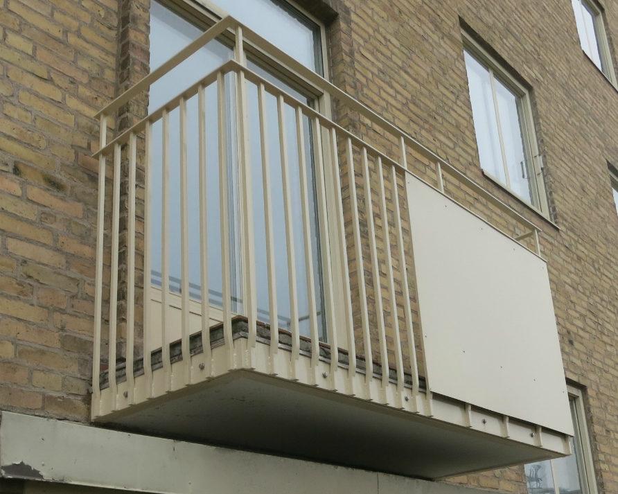 Balkong med gult räcke vid balkongrenovering på Brf Hästhagen i Malmö