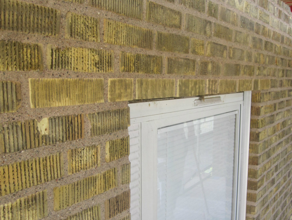 Gul fasad med utbytt tegelbalk och betsat tegel