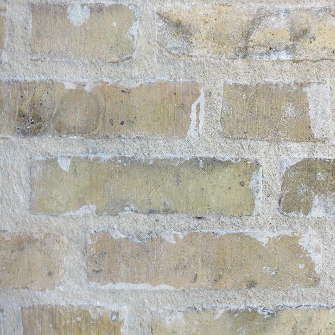 Närbild på gul tegelvägg med utsmetade fogar efter oprofessionellt utförd fogning