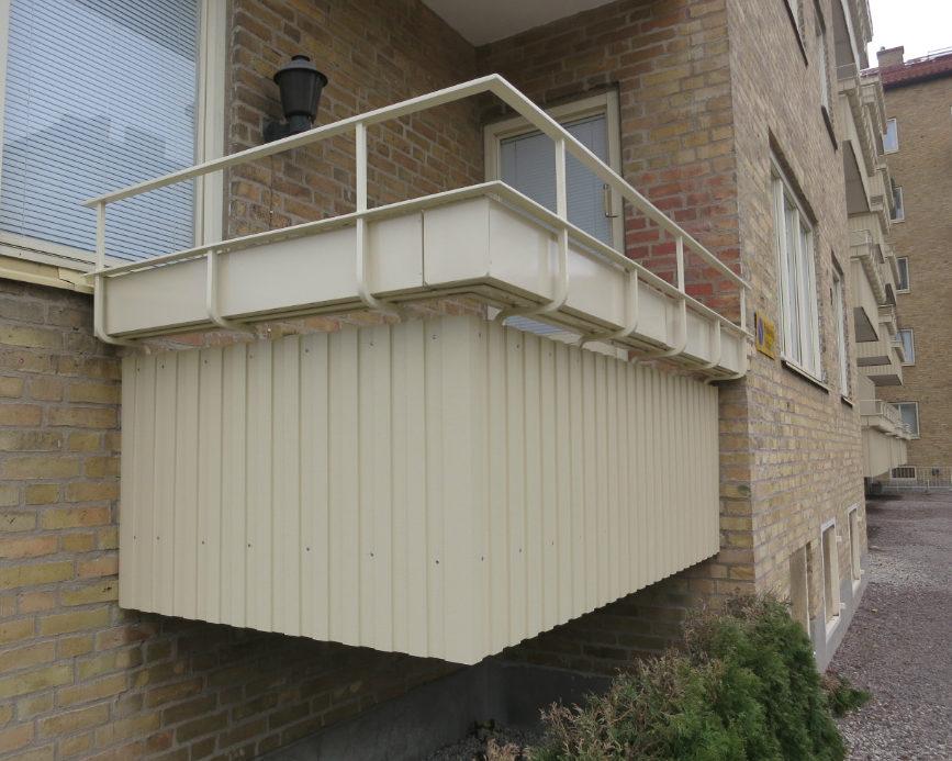 Gul balkong med plåt och smidesräcke i samband med balkongrenovering