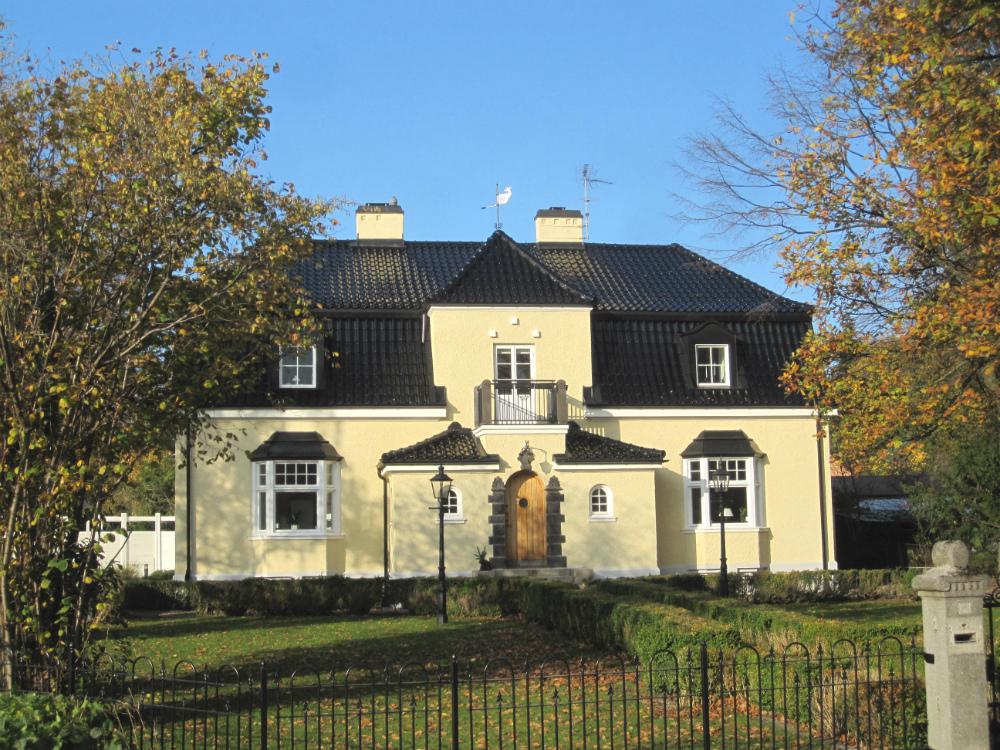 Gul fastighet med svart tak av glaserat tegel