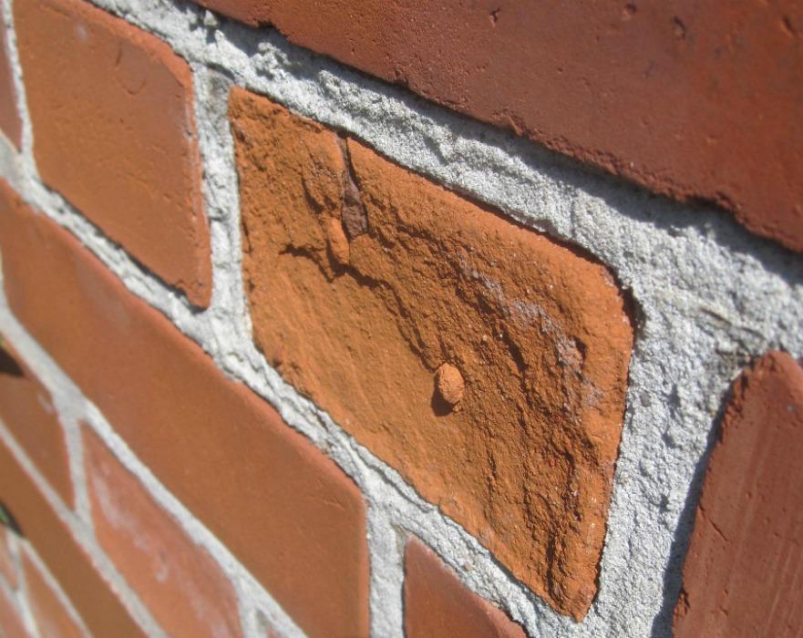 Närbild på röda vittrade tegelstenar vid fasadrenovering i Landskrona