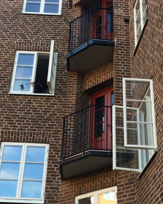 Svarta balkonger mot en brun tegelfasad. Vita fönster pryder också fasaden.