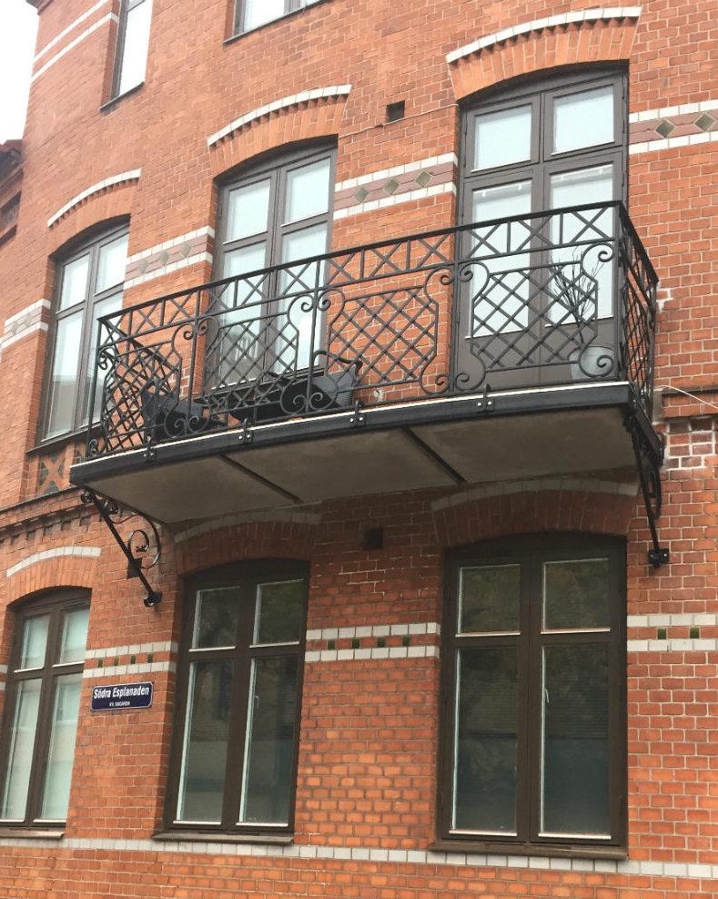 Vacker svart smidesbalkong mot äldre röd tegelfasad i samband med renovering av balkongerna