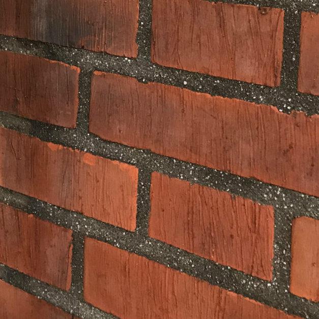 Svartgrå tegelfog med marmorkross i Brf Cederns röda tegelfasad.