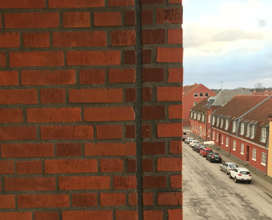 Närbild på det färdiga resultatet av den svarta fogen mot den röda fasaden. Till höger skymtas den pittoreska gatan där Brf Cedern ligger